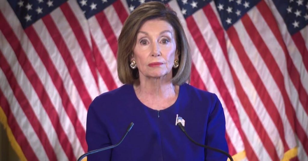 Nancy Pelosi standing in front of American Flags