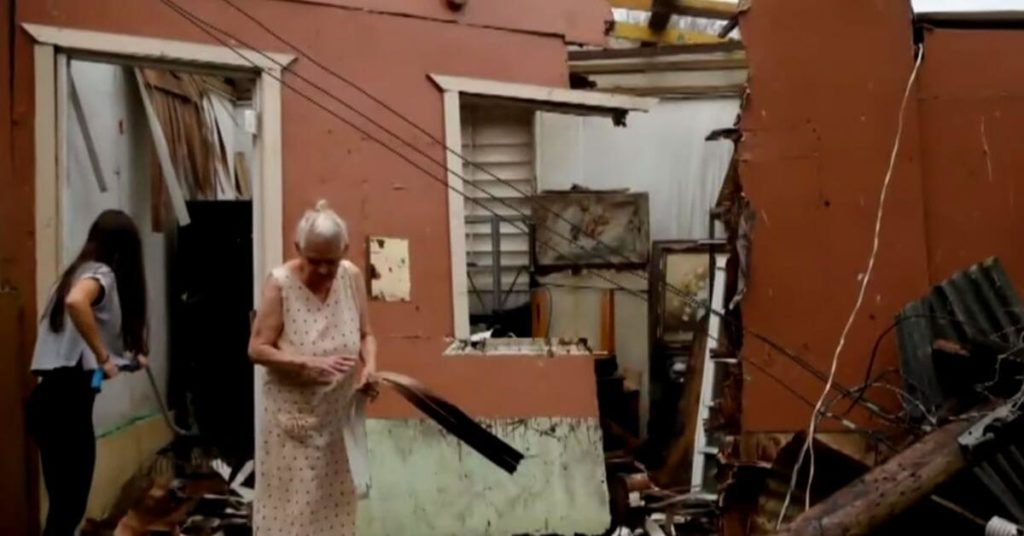 Woman next to her damaged home