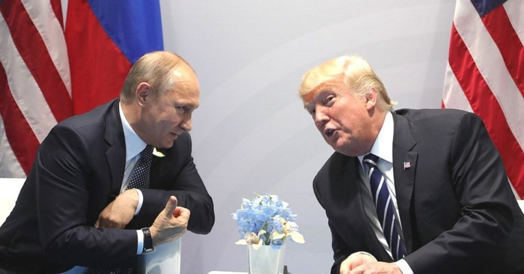 Trump leaning over to speak to Putin