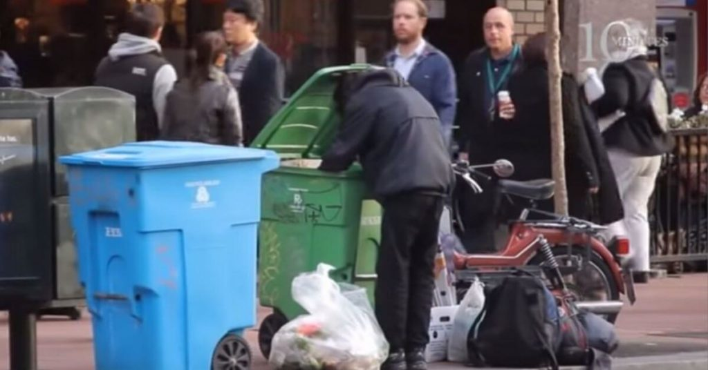 A homeless person digging in a trash can on a busy street.