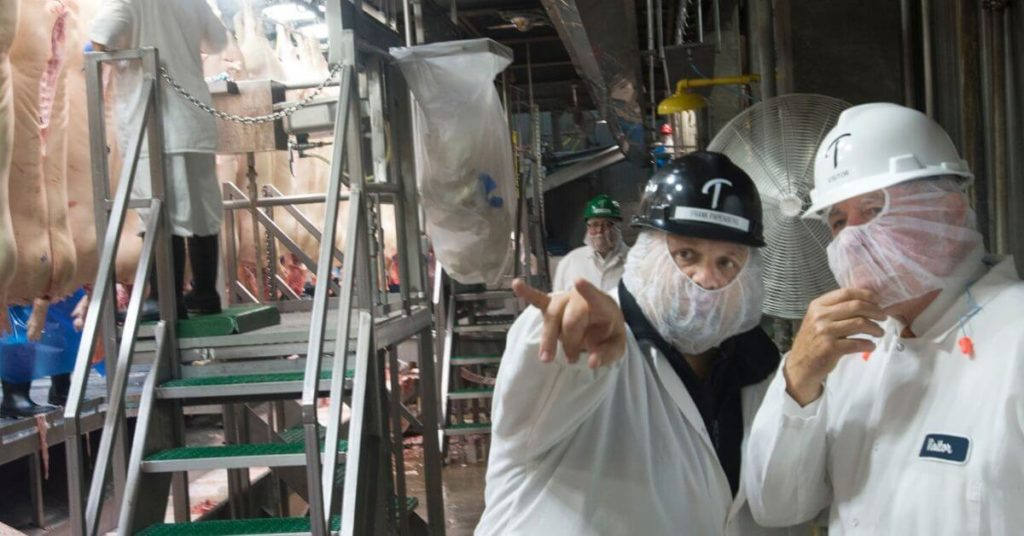 Two workers inside a meat processing plant