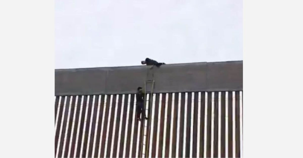 Three men quickly scale a newly built portion of the border wall