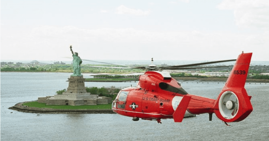 A helicopter flying over the statue of liberty