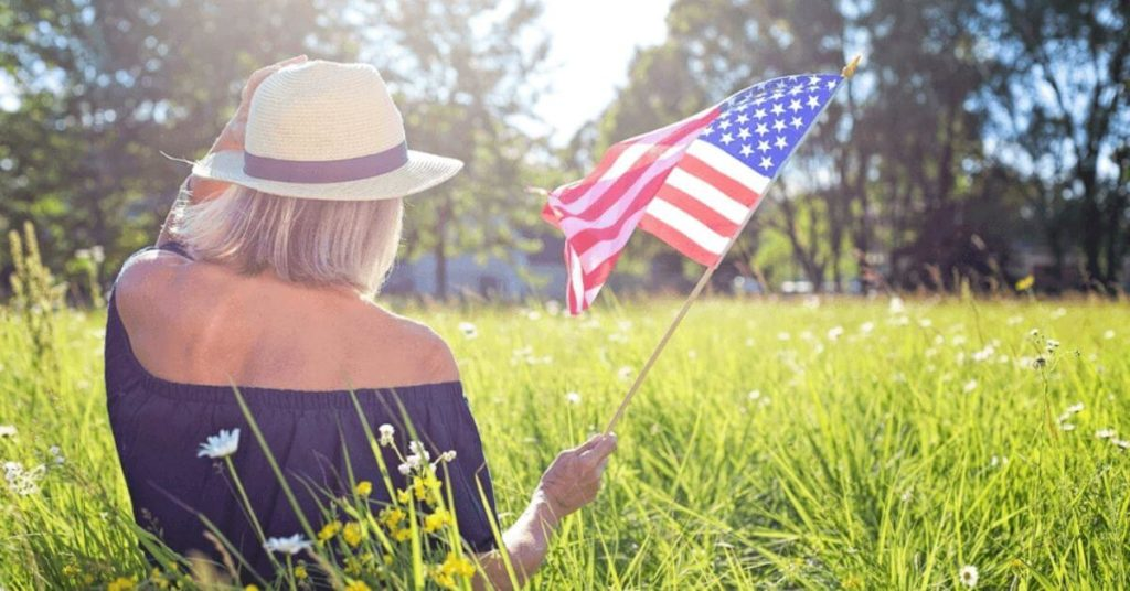 A girl sitting in the grass holding an American flag