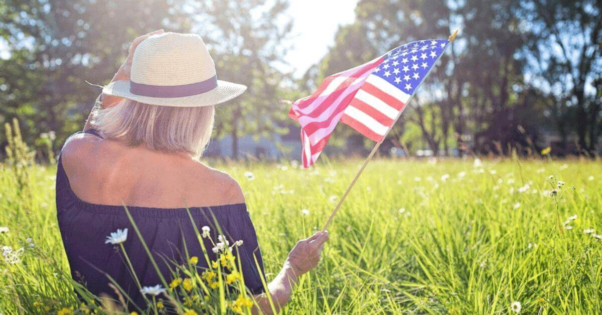 A photograph of a woman waving an American flag while sitting in a sunny field.