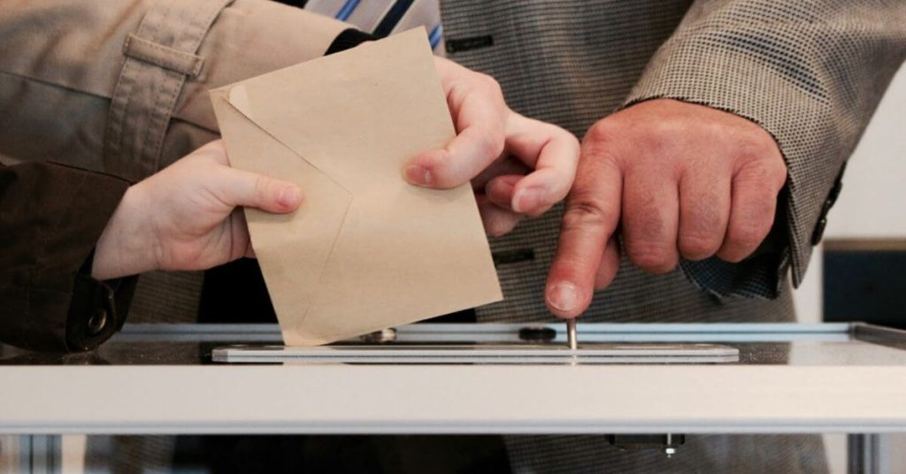 A photograph of a paper vote being inserted into a ballot box.