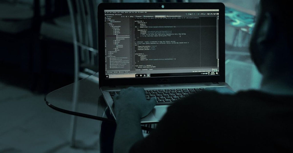 Shadowy image of a man sitting at a computer