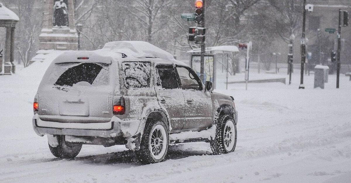 A vehicle driving on a snowy street