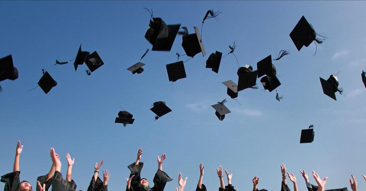 A photograph of graduates throwing their mortarboard caps in the air.