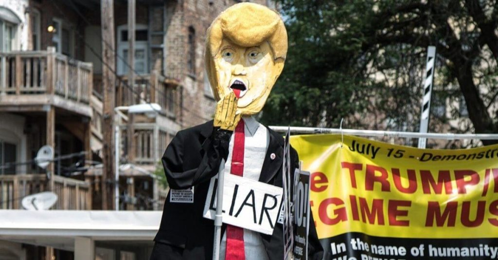 "A photograph of a parade figure of Donald Trump wearing a ""liar"" sign."