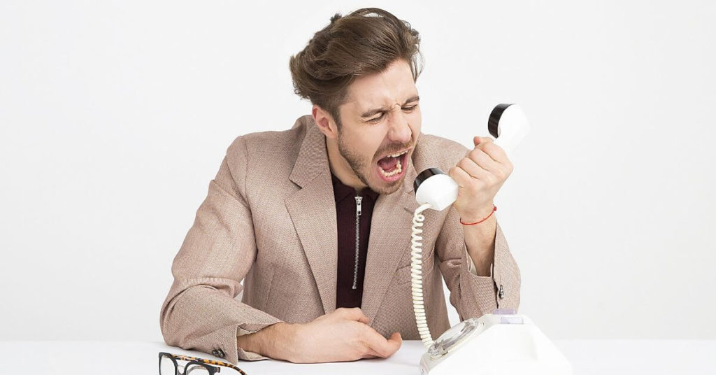 Angry man yelling into the telephone