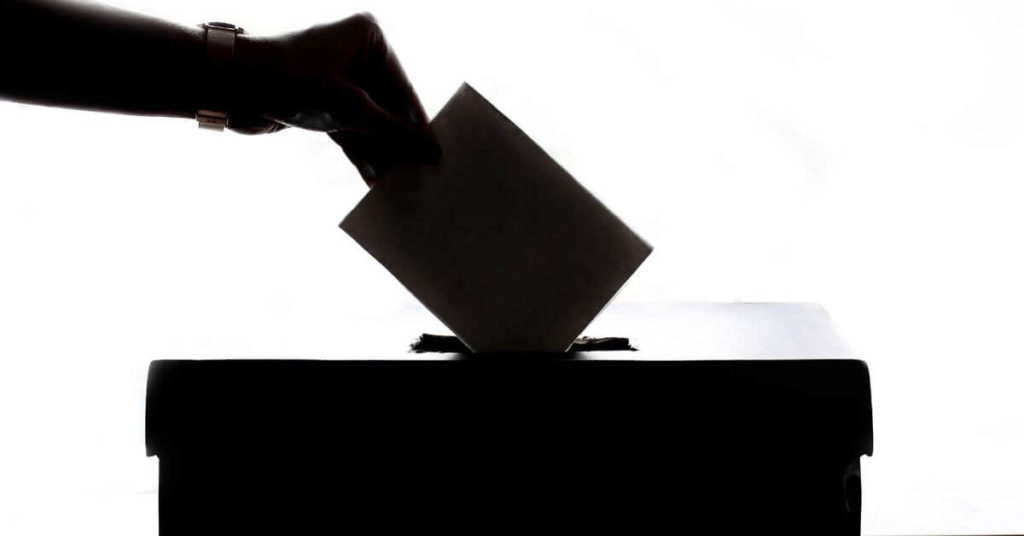 A hand placing a ballot in a box