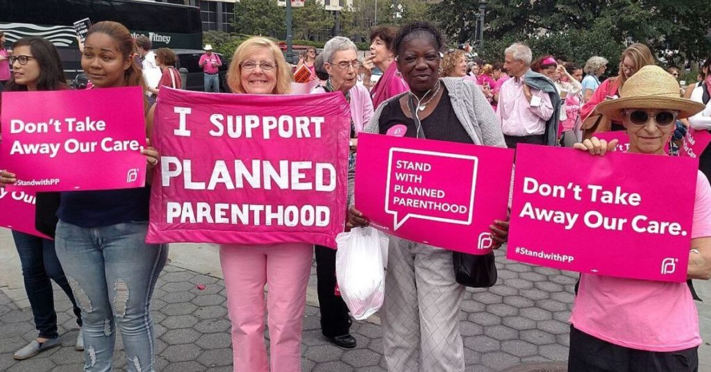 Women holding signs in support of planned parenthood