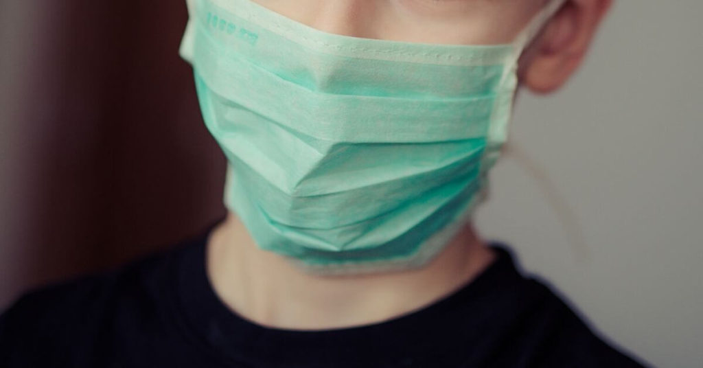 Close up photo of a person wearing a medical face mask