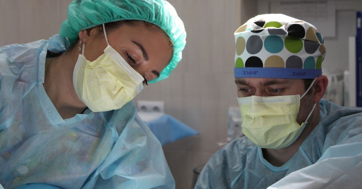 A photograph of 2 health care professionals in masks, working over a patient.