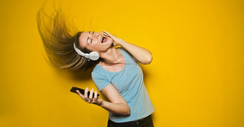 A woman wearing headphones and dancing in front of a yellow background