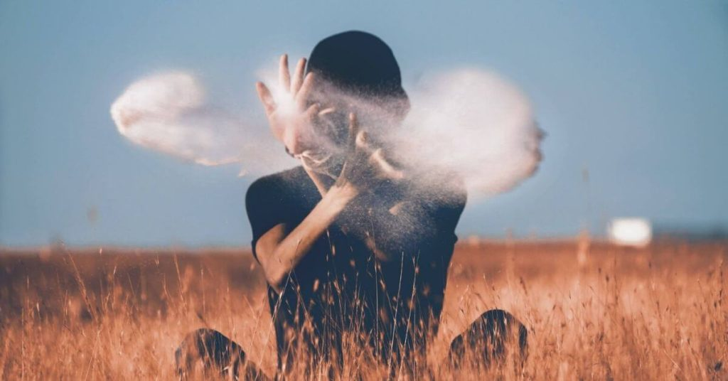A person sitting in a field throwing a handfull of smoke