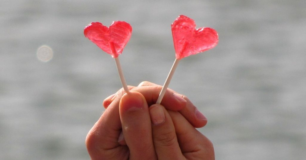 A hand holding two heart-shaped lollypops