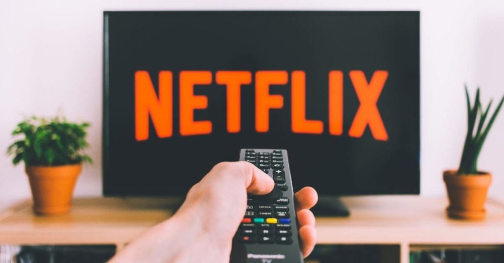 A photo of a hand holding a remote pointing it at a TV with Netflix on it