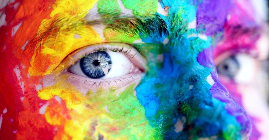 Close up of a face painted with the rainbow flag