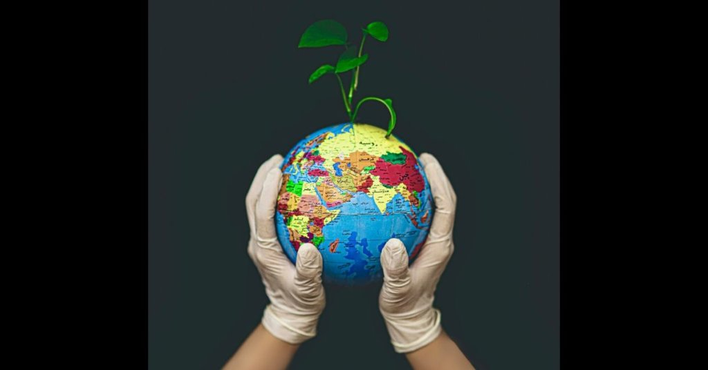 Gloved hands support a globe with a tiny plant sprouting from the top.