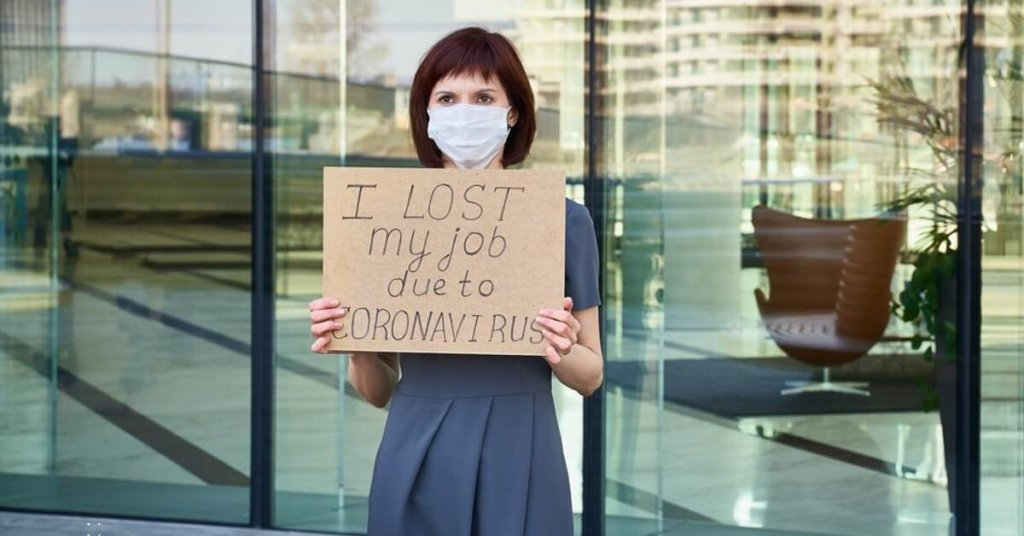 """Woman holding a sign that says """"I lost my job due to coronavirus"""""""