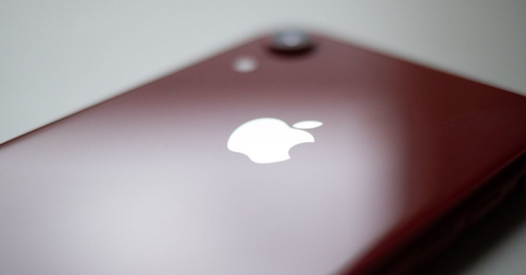 The back of a red iPhone lying on a white counter