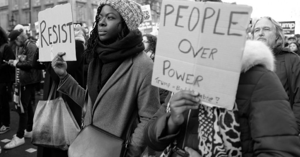 African American protestors holding signs that say Resist and People Over Power