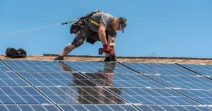 Man installing solar panels to a roof