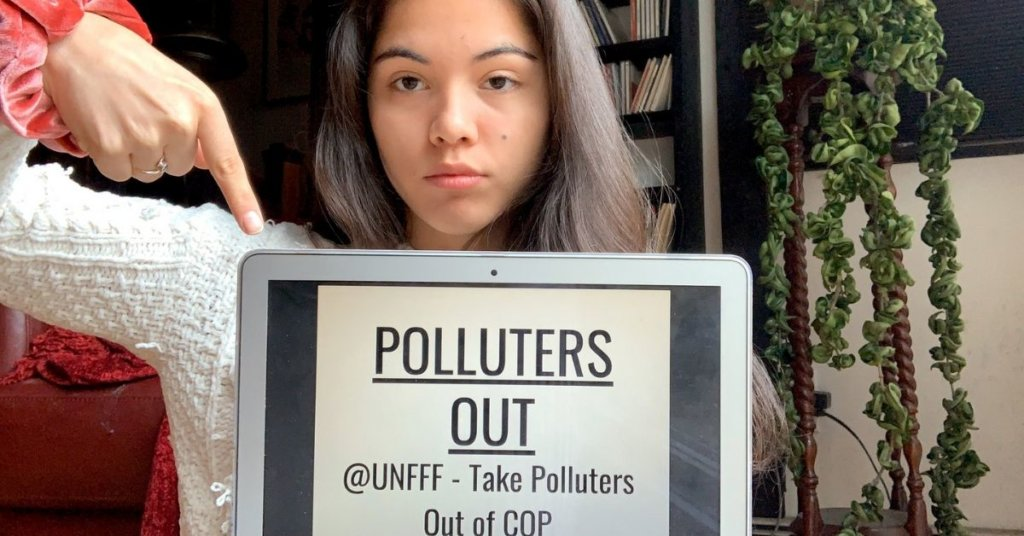 """Xiye Bastida holding a laptop with """"Polluters Out"""" on it"""