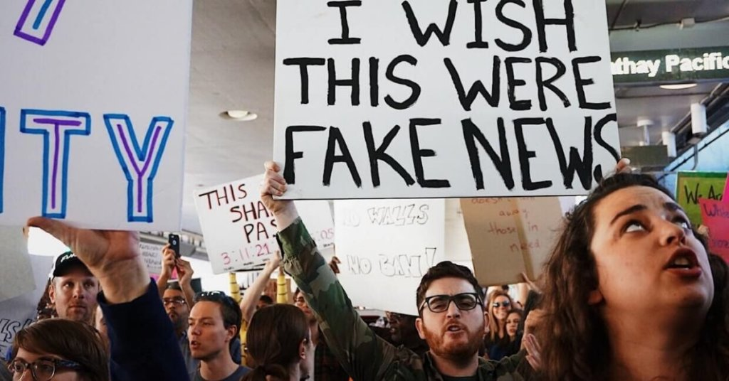 "Protest with one man holding a sign that says ""I wish this were fake news"""