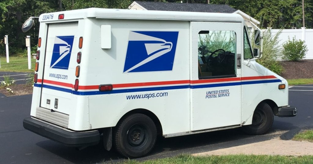 A postal truck driving down a road