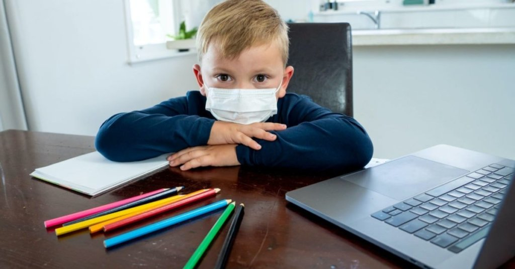 Child at a table wearing a facemask