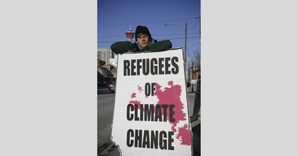 Person holding a refugee of climate change sign