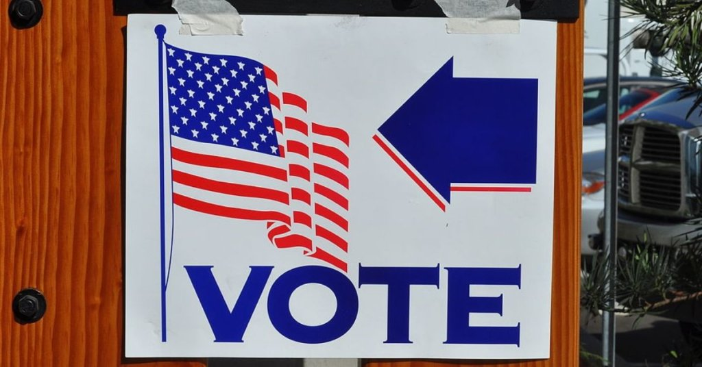 A photograph of a Vote sign with arrow and american flag