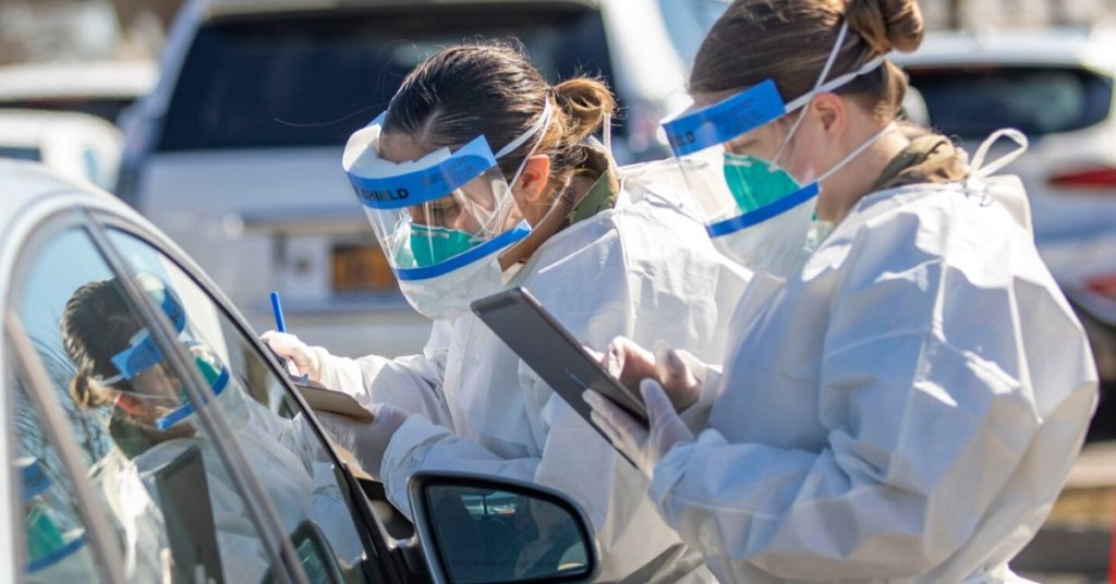 A photograph of healthcare workers at a drive thru coronavirus testing site.