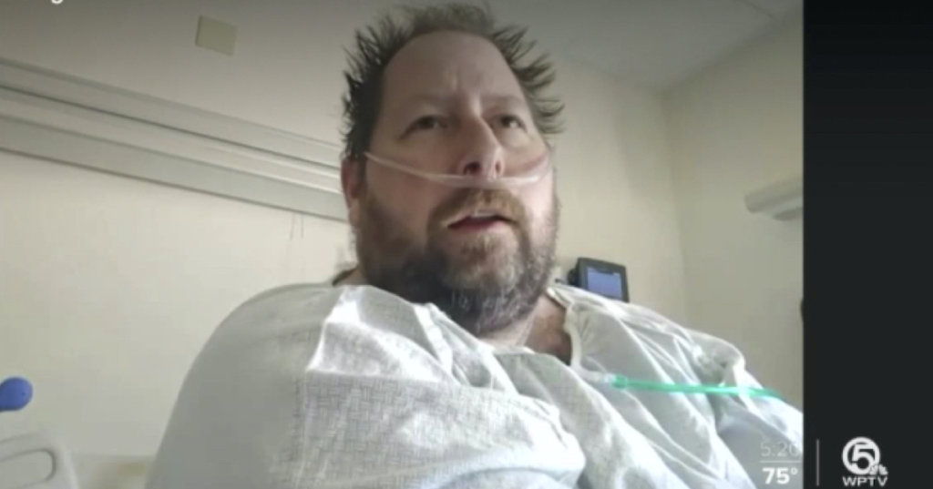 A photograph of a man sitting in a hospital gown.