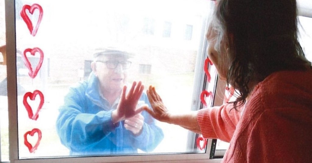 A photograph of two seniors touching opposite sides of a window.