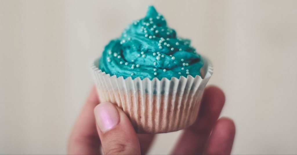 A hand holding a cupcake with teal frosting