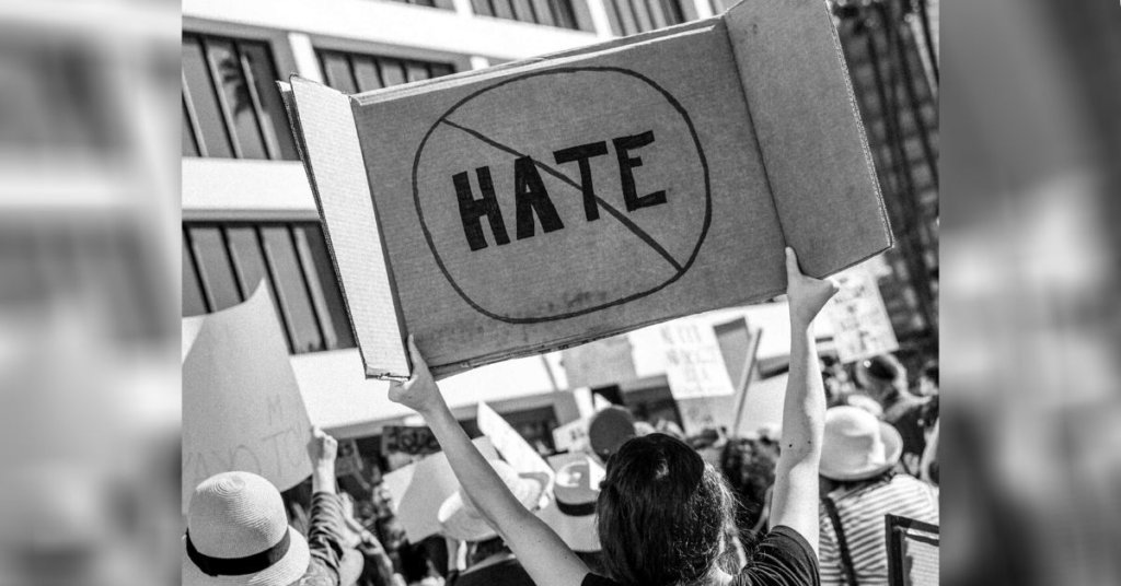 A photograph of protestors. One carries and anti-hate sign.