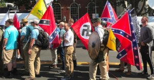 A photograph of men marching with Nazi and Confederate flags.