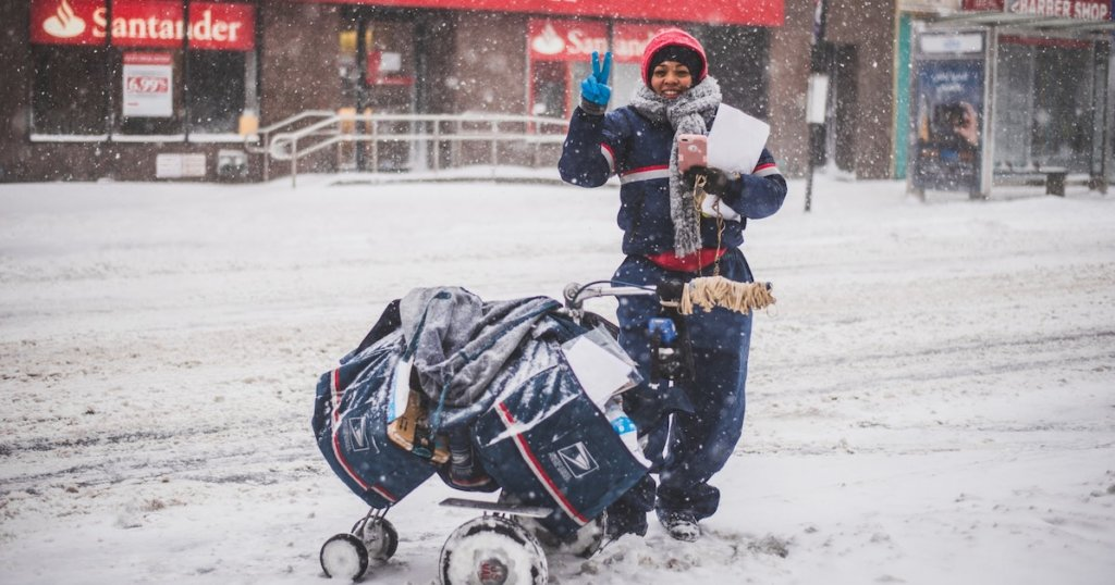 A photograph of a letter carrier in the snow with an overloaded trolley of mail. She is giving the peace sign.