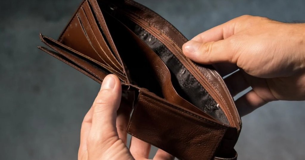 A person holding open an empty wallet