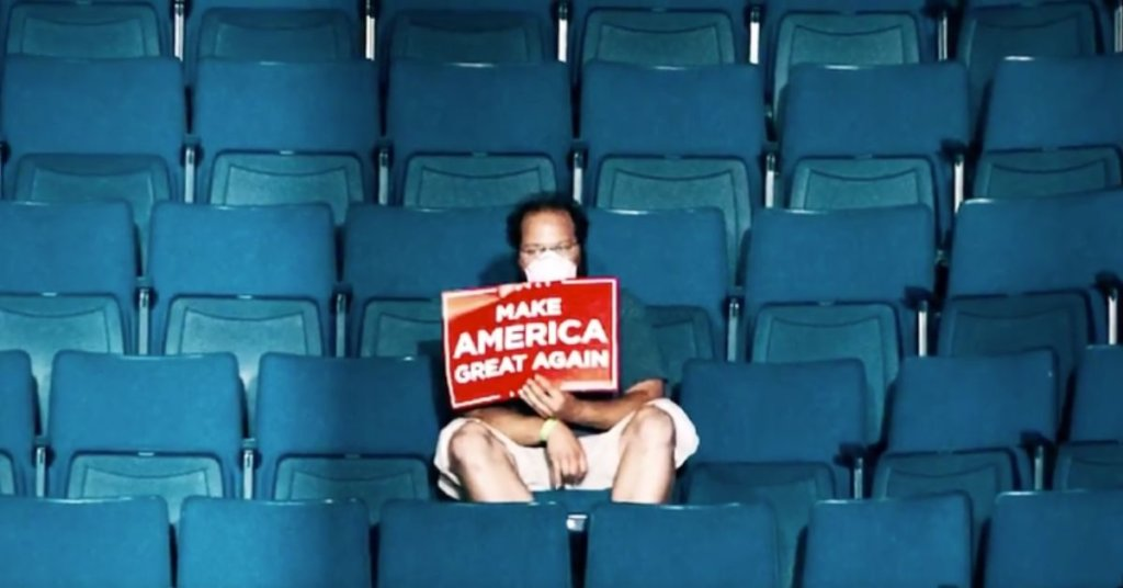 A photograph of a single Trump supporter sitting alone in arena seats.