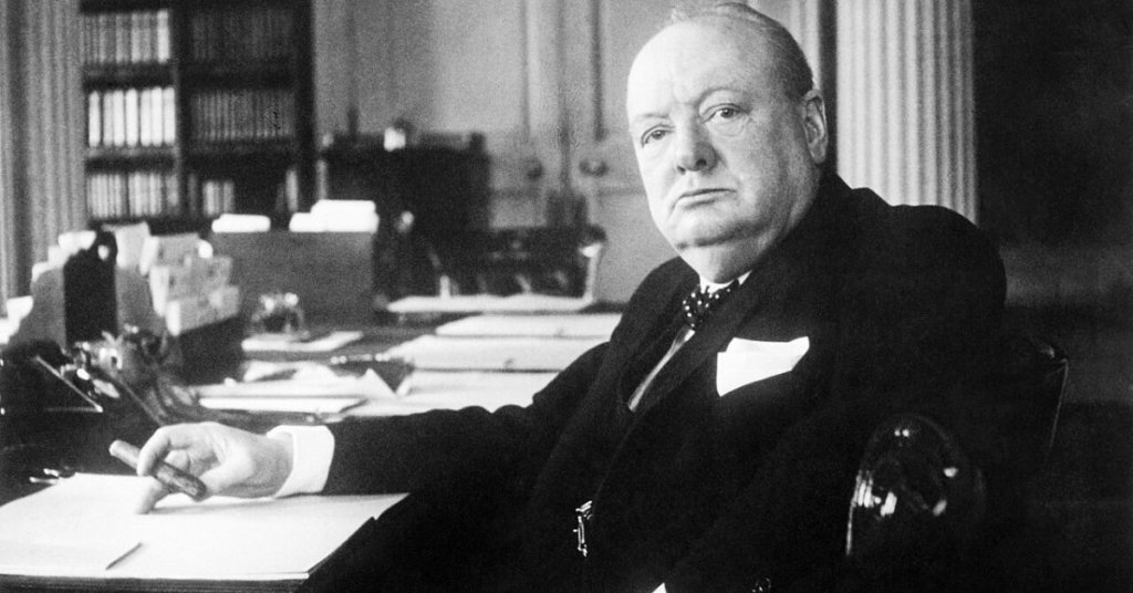 Black and white photo of Churchill sitting at a desk