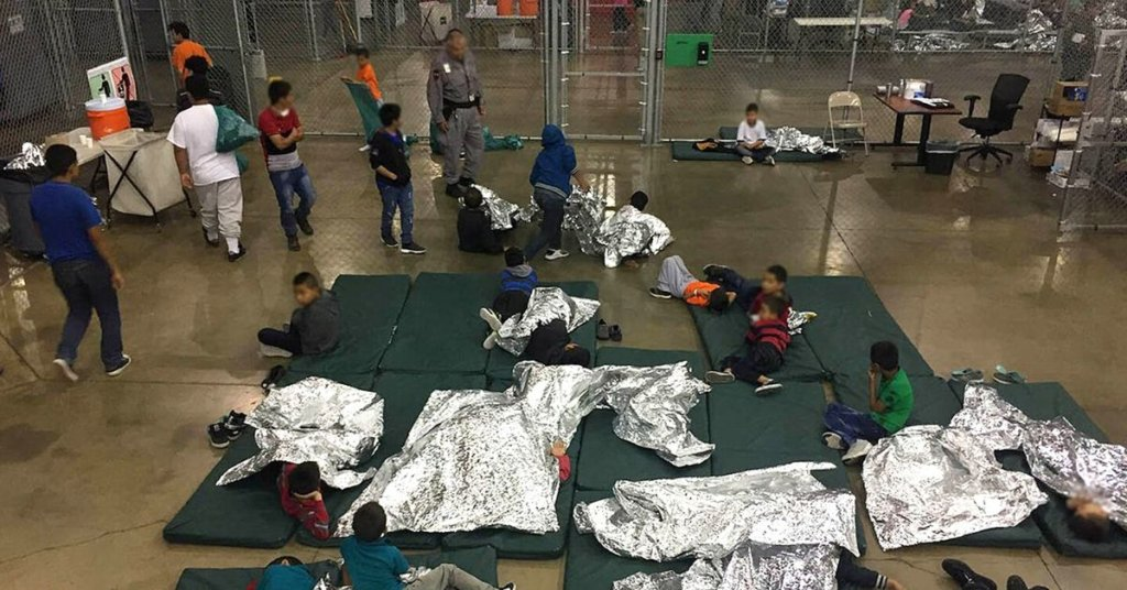 A photograph of a children's detention facility. Sleeping mats and foil blankets lie together on a concrete floor near the center of a fenced in area.