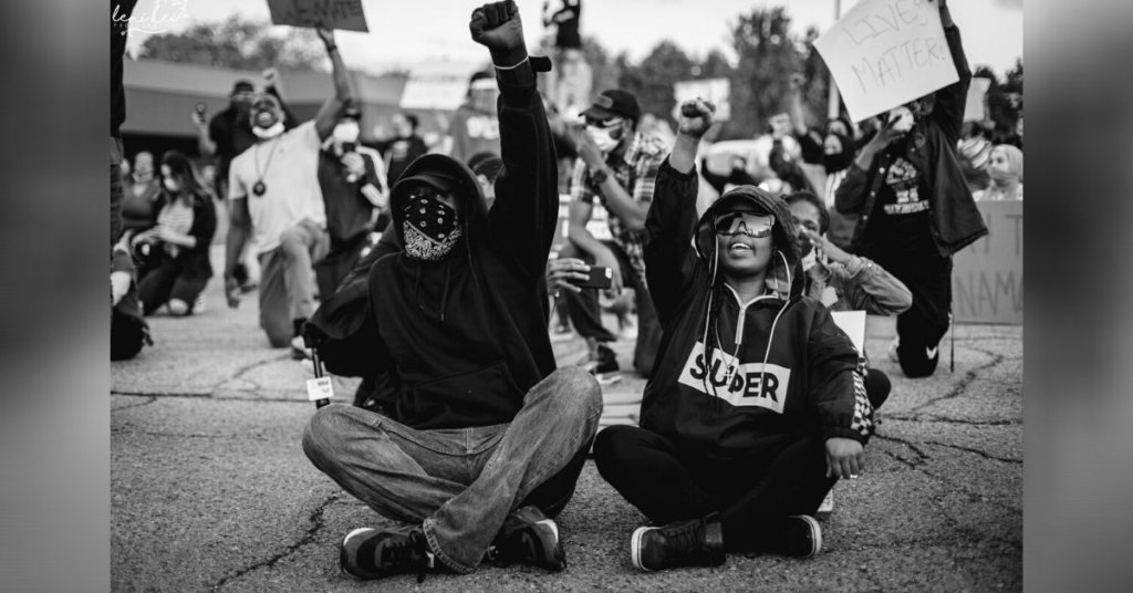 Quajuan Adams and Ramonica Anderson sitting on the ground with their fists in the air