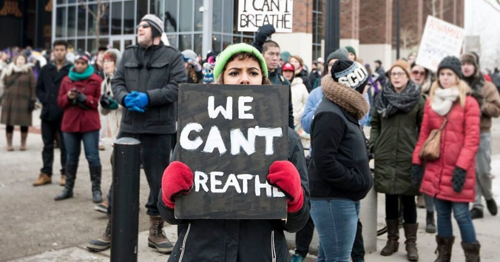 """Woman at a BLM protest holding a sign that says """"We can't breath"""""""