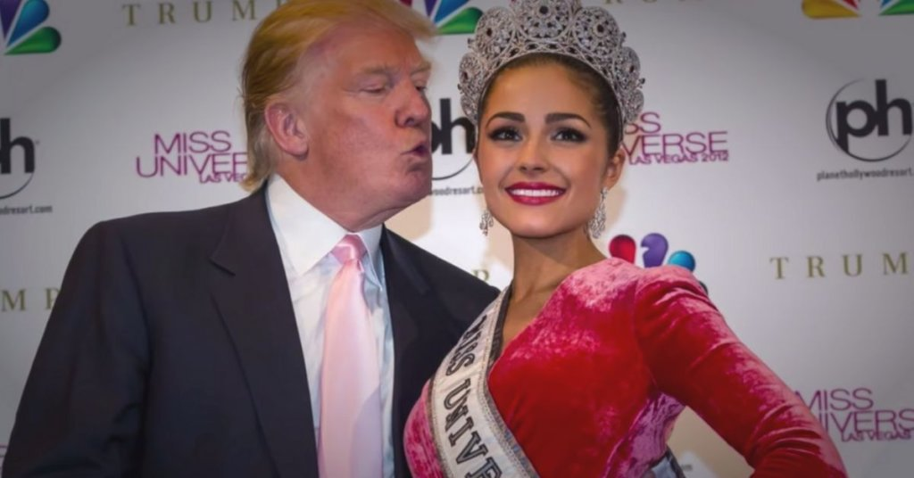 A photograph of Donald Trump leaning his puckered lips toward a beauty pageant contestant during a photo shoot.
