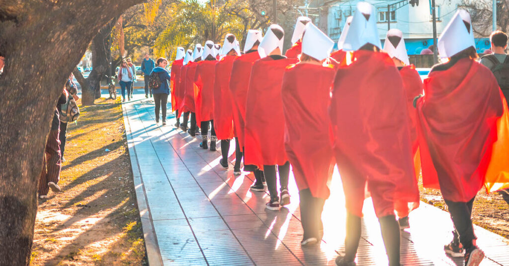 protesters march dressed as Handmaids.